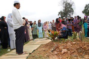 Hafifi melihat kubur anaknya sambil dibersihkan oleh isterinya